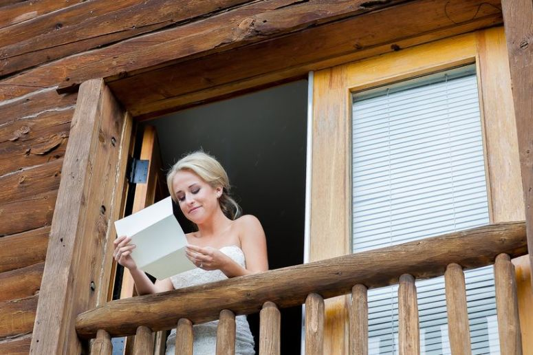 bride reading love note on wedding day