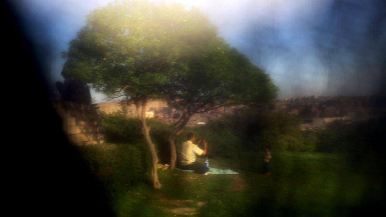 Un hombre fotografía a su pequeño hijo (casi oculto tras el velo) en una plaza pública en El Cairo, Egipto.
