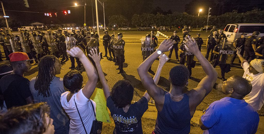"Protesters in Baton Rouge, LA shout ""Hands up, don't shoot"" as law enforcement stand watch (Getty Images)"