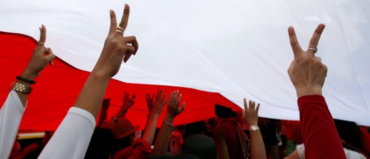 People gesture as they walk under a large Indonesian flag as they take part in a rally against what they see as growing racial and religious intolerance in the world
