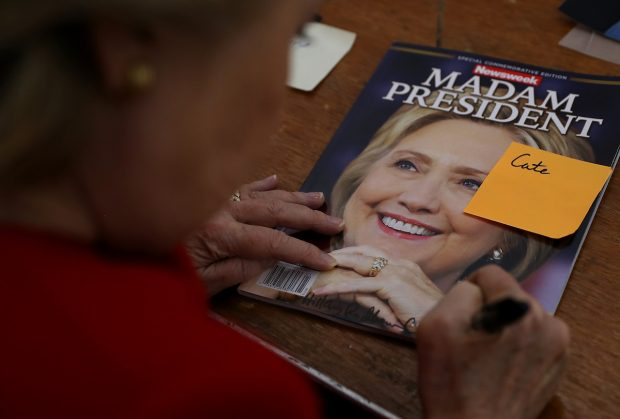 Democratic presidential nominee former Secretary of State Hillary Clinton signs an autograph on a Newsweek 'Madam President' commemerative magazine backstage after a campaign rally on November 7, 2016 in Pittsburgh, Pennsylvania. (Justin Sullivan/Getty Images)