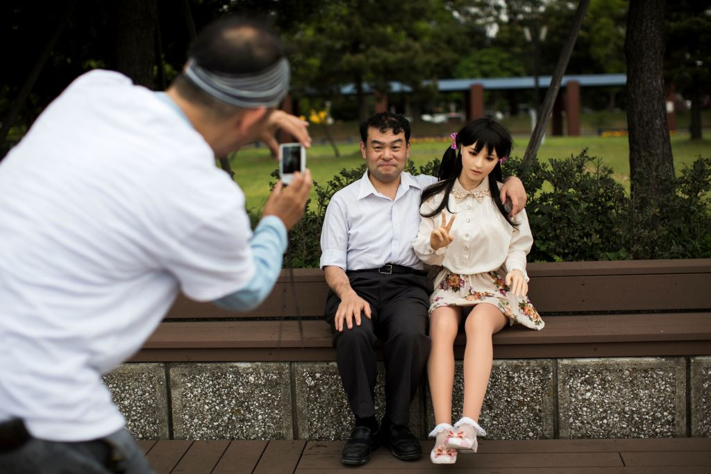 In this picture taken on May 9, 2017, a man takes pictures of physiotherapist Masayuki Ozaki and his silicone sex doll Mayu in Tokyo Bay. (Photo: BEHROUZ MEHRI/AFP/Getty Images)