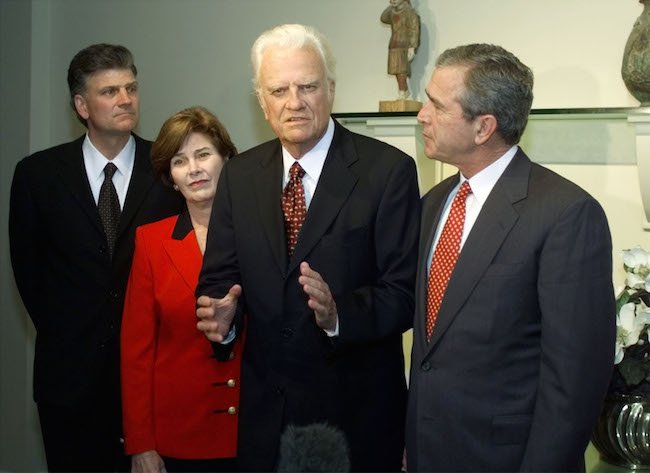Rev. Billy Graham praises Republican presidential candidate George W. Bush in a meeting with press in Jacksonville, Florida, November 5, 2000. Billy Graham's son Franklin and Laura Bush look on. REUTERS