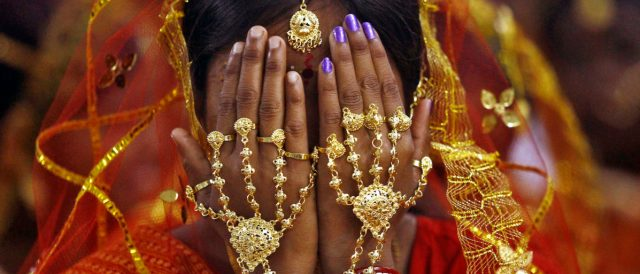 A bride covers her face as she waits to take her wedding vow at a mass marriage ceremony at Bahirkhand village, north of Kolkata February 8, 2015. A total of 108 tribal Muslim and Hindu couples from various villages across the state took their wedding vows on Sunday during the day-long mass marriage ceremony organised by a social organisation, the organisers said.  REUTERS/Rupak De Chowdhuri
