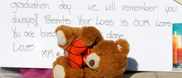 A stuffed toy slumps over in front of a sign at a makeshift memorial on a fence close to Marjory Stoneman Douglas High School three days after the school shooting in Parkland, Florida, U.S., February 17, 2018. REUTERS/Jonathan Drake
