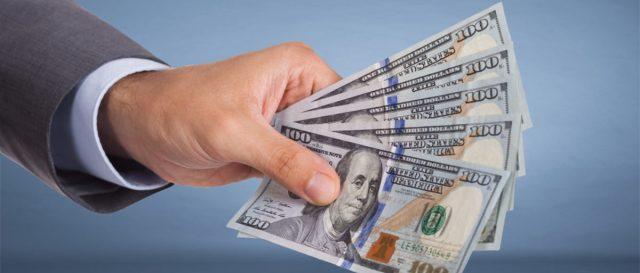 A man doles out money. (Shutterstock/Andrey_Popov)