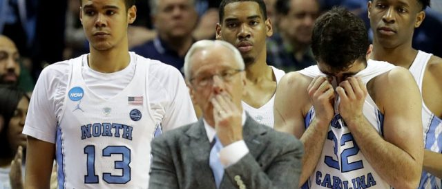 Head coach Roy Williams of the North Carolina Tar Heels and his team react to their 86-65 loss to the Texas A&M Aggies during the second round of the 2018 NCAA Men's Basketball Tournament at Spectrum Center on March 18, 2018 in Charlotte, North Carolina.  (Photo by Streeter Lecka/Getty Images)