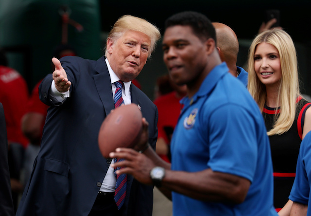 President Donald Trump talks to his daughter and advisor Ivanka Trump as they watch former NFL star Herschel Walker throw a football during the White House Sports and Fitness Day event on the South Lawn of the White House in Washington, U.S., May 30, 2018. REUTERS/Jonathan Ernst - RC1BCB02FEC0