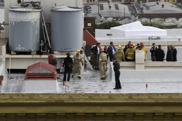 Authorities stand on the rooftop of the Cecil Hotel after a body was found in a water tank in Los Angeles, California, February 19, 2013. Police were trying to determine on Tuesday if a body found in a water tank on top of Cecil Hotel is that of a 21-year-old Canadian woman who went missing while staying there more than two weeks ago. Elisa Lam, a student from Vancouver, British Columbia who was visiting Southern California on her own, was last seen at the Cecil Hotel in downtown Los Angeles on January 31 and authorities had characterized her disappearance as suspicious. REUTERS/Jonathan Alcorn