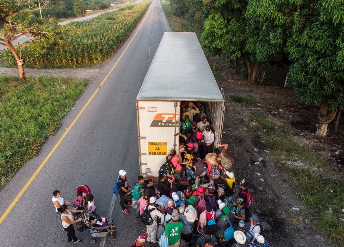 """Honduran migrants taking part in a caravan heading to the US, get on a truck, near Pijijiapan, southern Mexico on October 26, 2018. - The Pentagon is expected to deploy about 800 troops to the US-Mexico border, two US officials told AFP on Thursday, after President Donald Trump said the military would help tackle a """"national emergency"""" and called on a caravan of US-bound migrants to turn around. (Photo by Guillermo Arias / AFP)"""