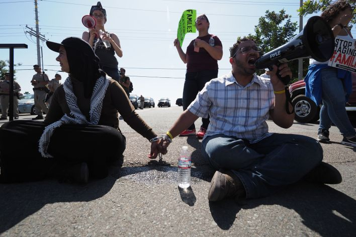 Protestors chained together at the wrist block traffic from passing on the road to the Otay Mesa Detention Center during a demonstration against US immigration policy that separates children from parents, in San Diego, California June 23, 2018. ROBYN BECK/AFP/Getty Images