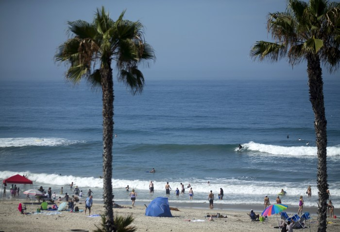 People gather at the beach to cool off as a heat wave brings high temperatures and humidity to Oceanside, California