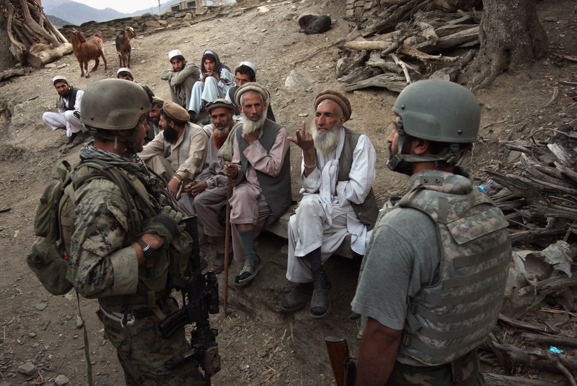 KORENGAL VALLEY, AFGHANISTAN - OCTOBER 25: Village elders speak with a U.S. Marine (L), through an interpreter as American and Afghan forces search for weapons October 25, 2008 in the Korengal Valley of Kunar Province in eastern Afghanistan. (Photo by John Moore/Getty Images)