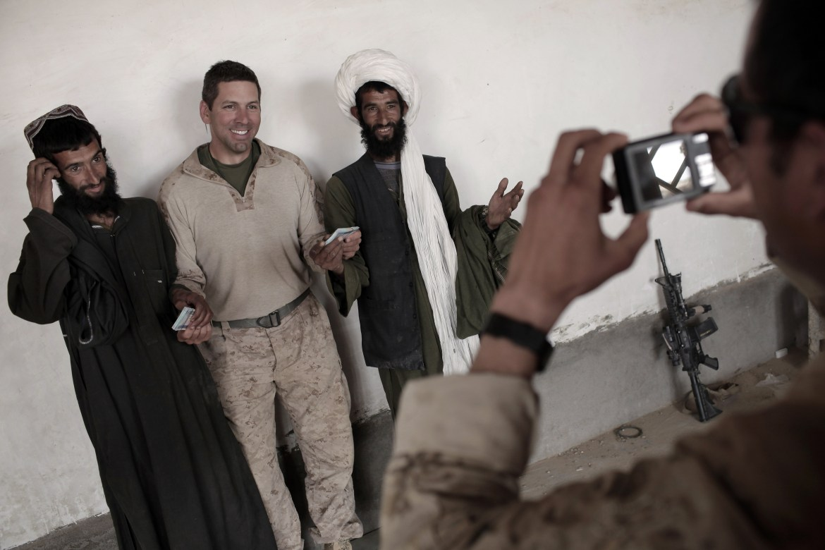 An interpreter for U.S. Marines of India Company, 3rd Battalion, 6th Marines takes a souvenir picture requested by the US officer giving 20,000 Afghanis each to two brothers for damages to their residences caused during the ongoing US military offensive against Taliban insurgency, in Marjah, Helmand province, southern Afghanistan, on April 12, 2010. (MAURICIO LIMA/AFP/Getty Images)