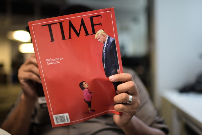 An AFP journalists reads a copy of Time Magazine with a front cover using a combination of pictures showing a crying child taken at the US Border Mexico and a picture of US President Donald Trump looking down, on June 22, 2018 in Washington DC. (Photo by ERIC BARADAT/AFP/Getty Images)
