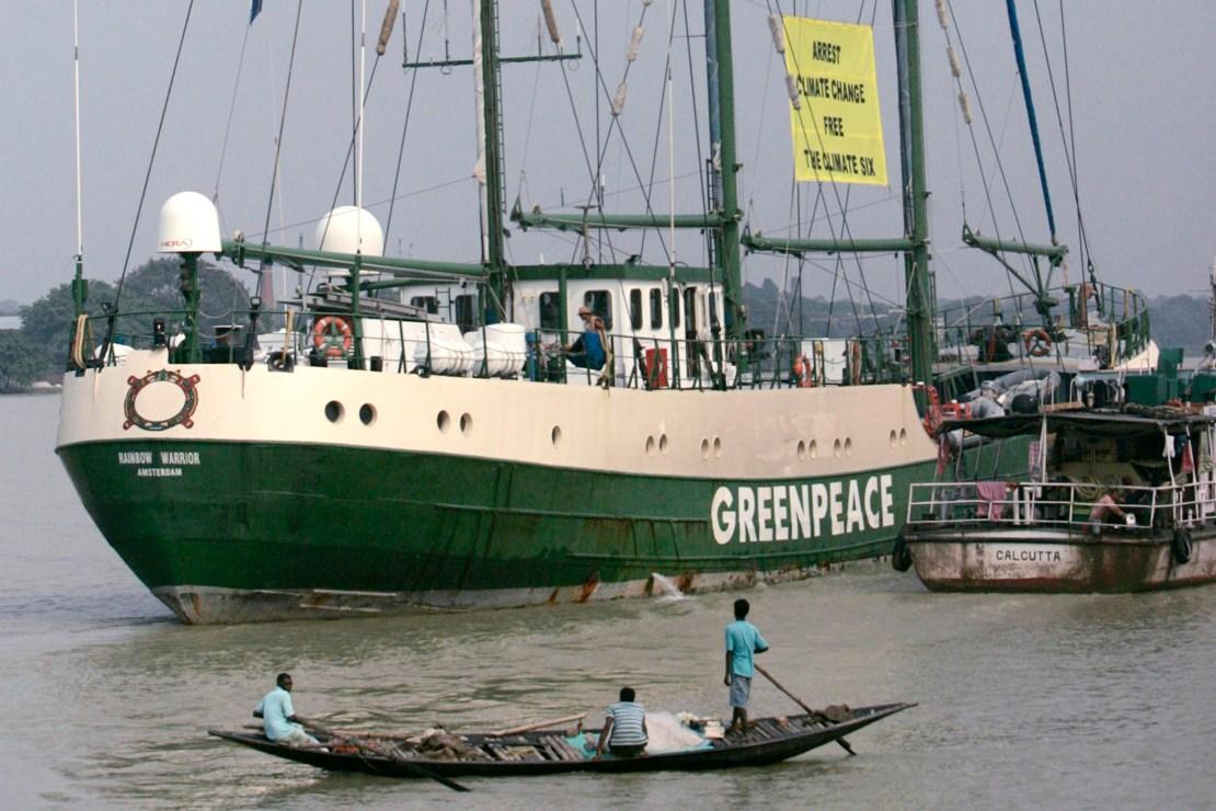 "Fishermen watch the Green peace ship ""Rainbow Warrior"" sail on the river Hooghly in Kolkata"