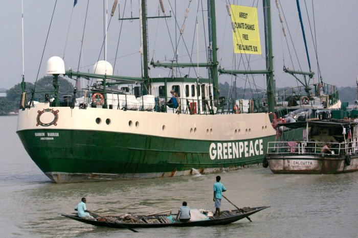 "Fishermen watch the Green peace ship ""Rainbow Warrior"" sail on the river Hooghly in Kolkata"