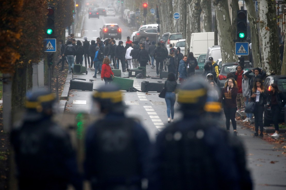 French riot police face off with youth and high school students during a protest against the French government's reform plan, in Bordeaux