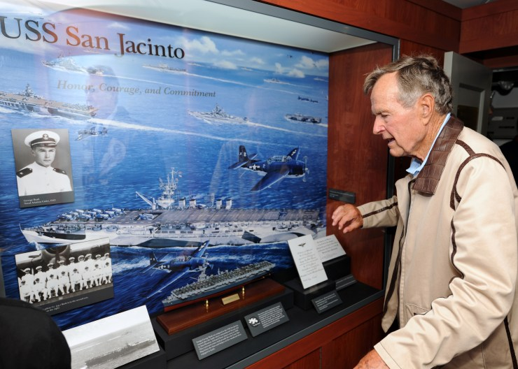 ATLANTIC OCEAN - JULY 14: In this handout image provided by the U.S. Navy, former President George H.W. Bush looks at a display of his former ship, the aircraft carrier USS San Jacinto (CVL 30), in the tribute room of the aircraft carrier that bears his name, USS George H.W. Bush (CVN 77) July 14, 2010 in the Atlantic Ocean. Bush and former first lady Barbara Bush spent their time onboard watching flight operations, touring the ship and visiting with the crew. The George H.W. Bush is conducting training in the Atlantic Ocean. (Photo by Nicholas Hall/U.S. Navy via Getty Images)