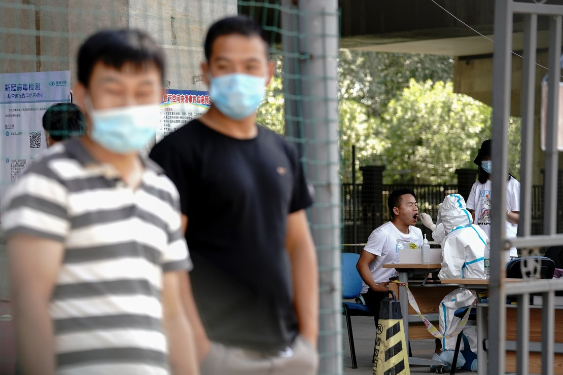 BEIJING, CHINA - JUNE 30: A medical worker wearing a protective suit takes a swap at a temporary COVID-19 testing site on June 30, 2020 in Beijing, China. As of today, the nucleic acid testing completed number of people in Beijing has reached 9 million. The authorities in Beijing have begun an operation to contain a potential second wave of coronavirus. (Photo by Lintao Zhang/Getty Images)