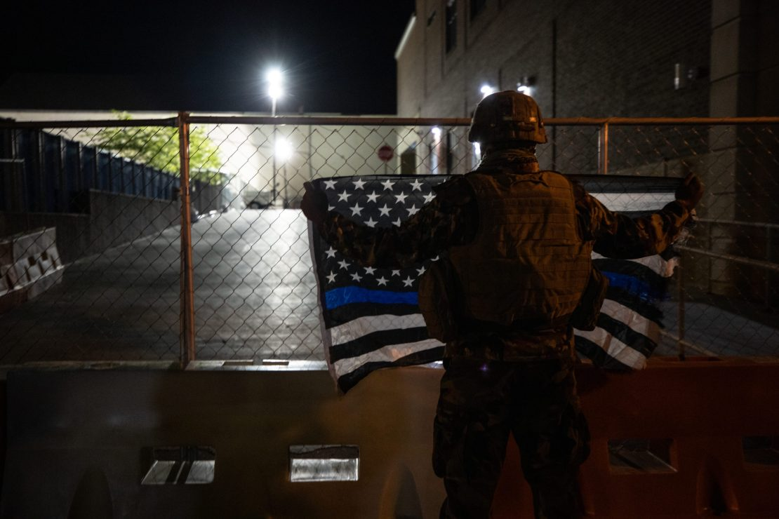 A man dressed in camouflage held a Thin Blue Line flag outside the Lancaster Bureau of Police Building, where officers were stationed. (Photo - Kaylee Greenlee / Daily Caller News Foundation)