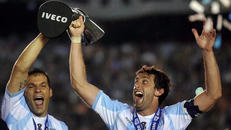 Diego Milito y Sebastian Saja. Racing sostiene la copa.