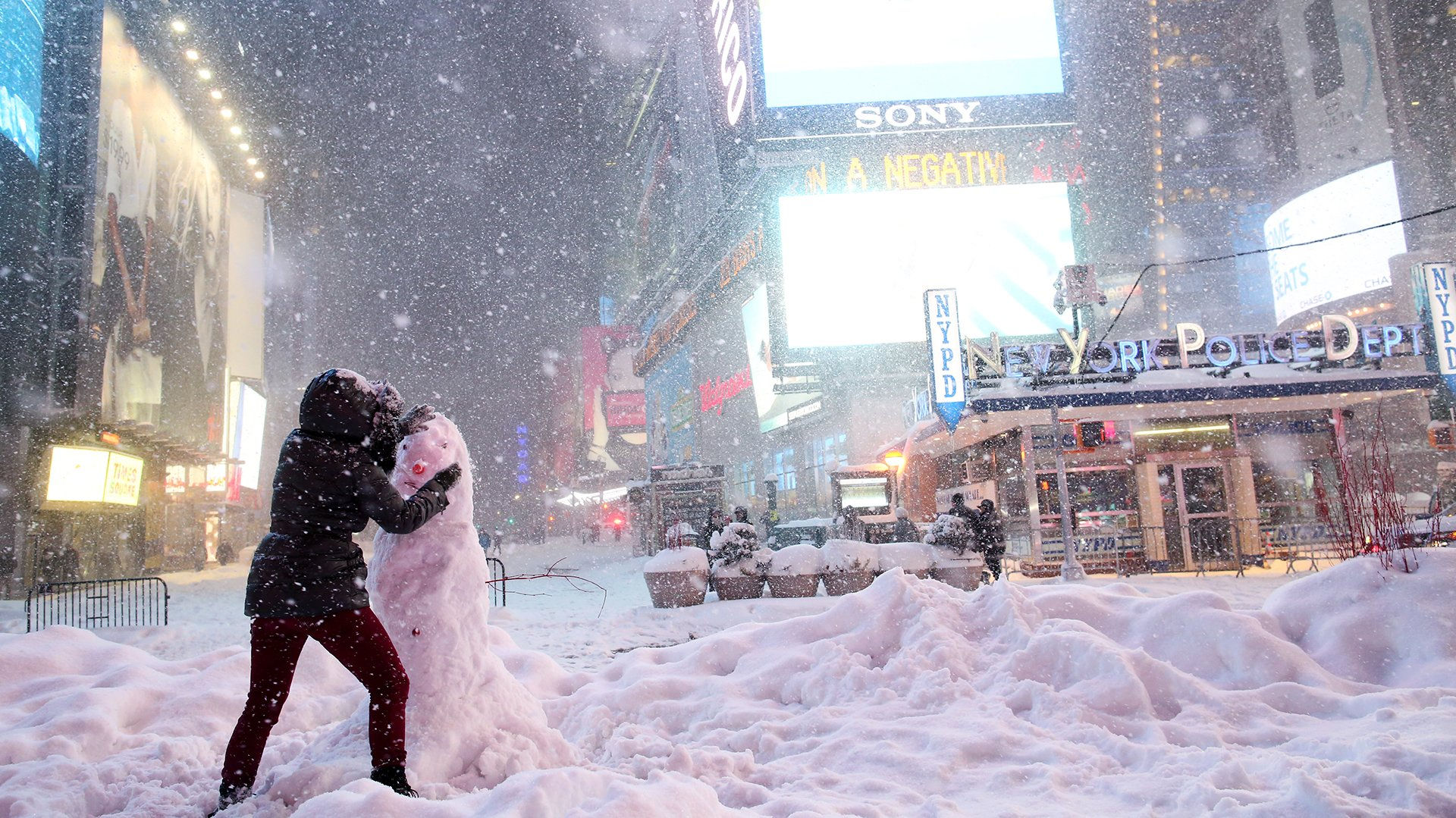 Algunos turistas se treven a salir a la calle y hacen muñecos de nieve