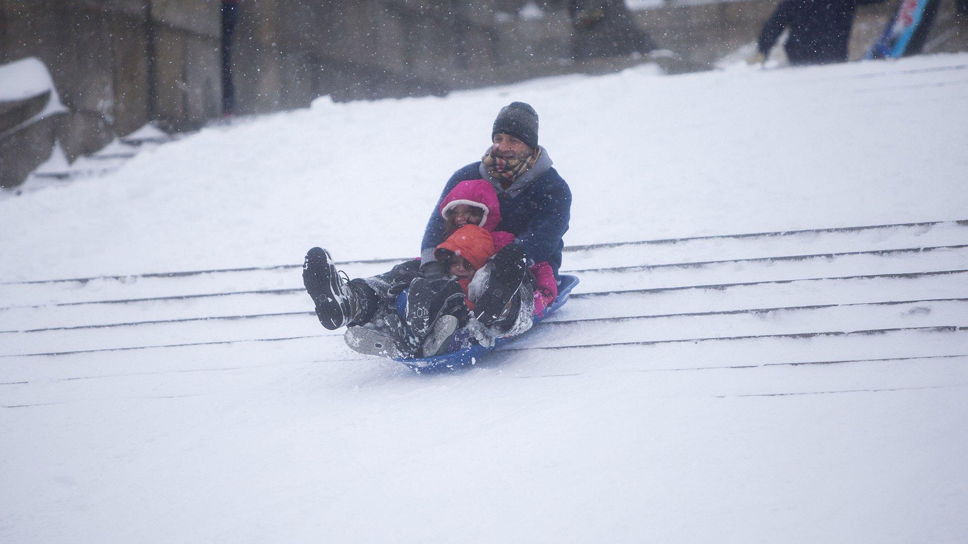 Un padre con sus hijos se lanzan en trineo