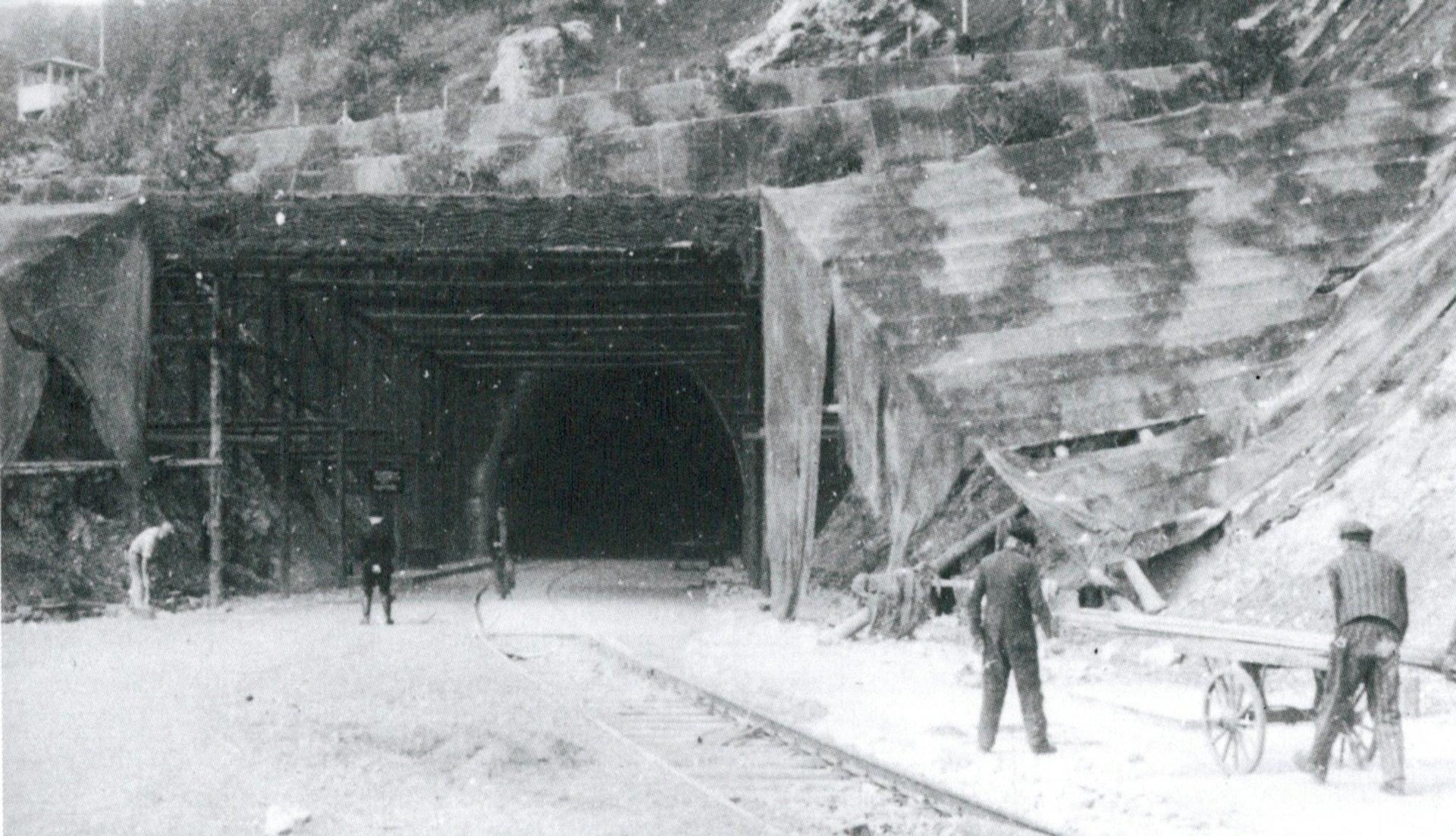 Un recluso del recinto secundario de Dora empuja un carro hacia la entrada del profundo sistema de túneles que albergaa la producción de cohetes V2. 1944