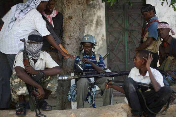 """Al-Shabab and Hizbul Islam militants take a break at a front-line section in sanca district in Mogadishu,  on July 21, 2009. Somalia's hard line Shabab militia yesterday raided the offices of three UN organisations hours after they banned their operations on accusation that they were """"enemies of Islam and Muslims. The armed group stormed the United Nations Development Programme, UN Department of Safety and Security and the UN Political Office for Somalia in two southern Somalia towns and impounded office equipment. The above foreign agencies have been found to be working against the benefit of the Somali Muslim population and against the establishment of an Islamic state in Somalia,"""" the Shebab said in a statement. AFP PHOTO/ MOHAMED DAHIR        (Photo credit should read MOHAMED DAHIR/AFP/GettyImages)"""