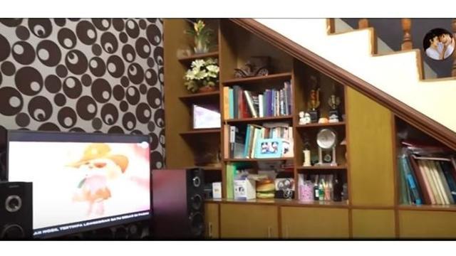 Ruang tv dirumah masa kecilnya tersebut terlihat nyaman dan terdapat buku yang ditata dengan rapi.