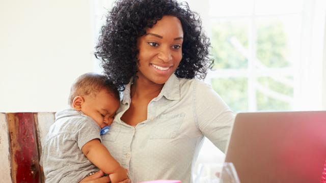 Seorang ibu yang sedang bekerja sambil mengurus anak