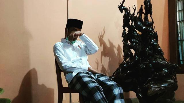 Jokowi terlihat duduk seorang diri di teras rumah ibunda di Solo, Jawa Tengah.