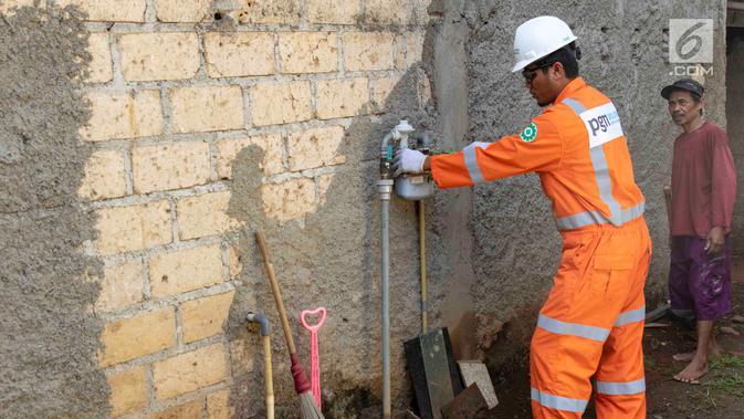 Petugas PT Perusahaan Gas Negara (PGN) memeriksa meteran jaringan gas bumi di perumahan warga di kawasan Cibinong, Bogor, Jawa Barat, Jumat (14/12). Pemerintah melalui PGN memberi tambahan 5.120 jargas pada tahun 2018. (Liputan6.com/Immanuel Antonius)