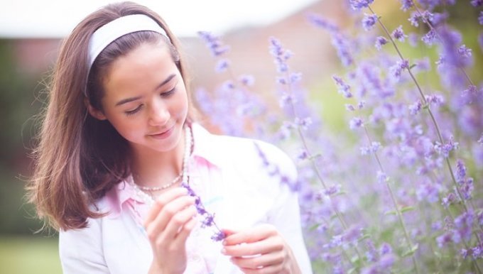 Portrait of teenage girl by purple catmint