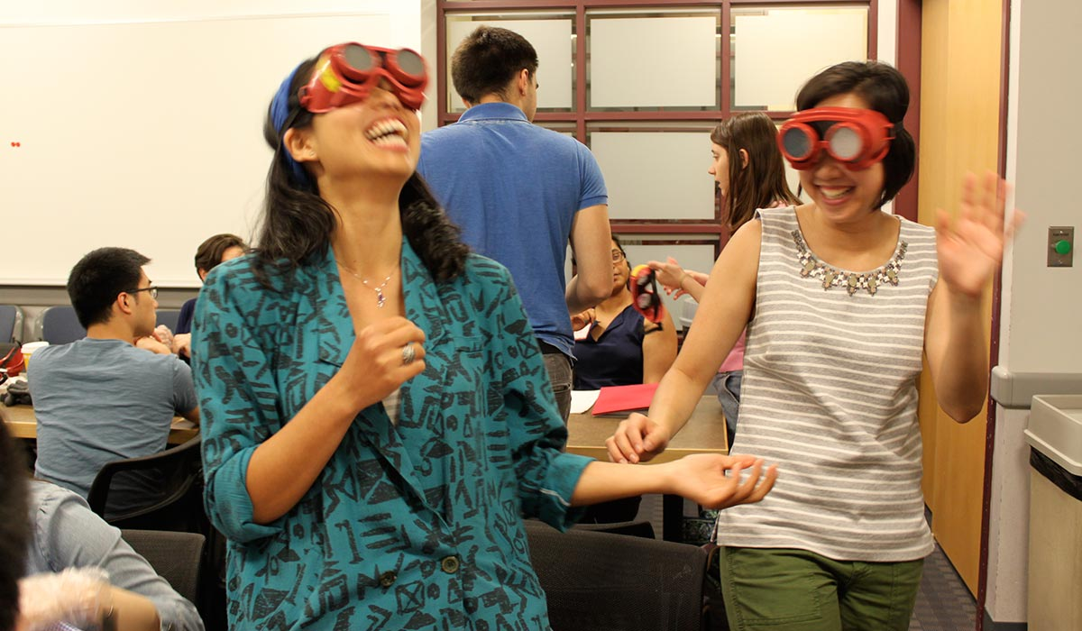Grace Teo and Alice Tin try on goggles that mimic eye diseases at the MIT AgeLab. Photo by Laura Hanson.