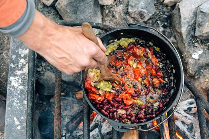 Cooking beans and vegetables in a Dutch oven over a campfire for vegetarian chili