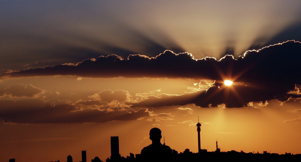 A man watches the sun set in as he overlooks the skyline in Johannesburg, South Africa