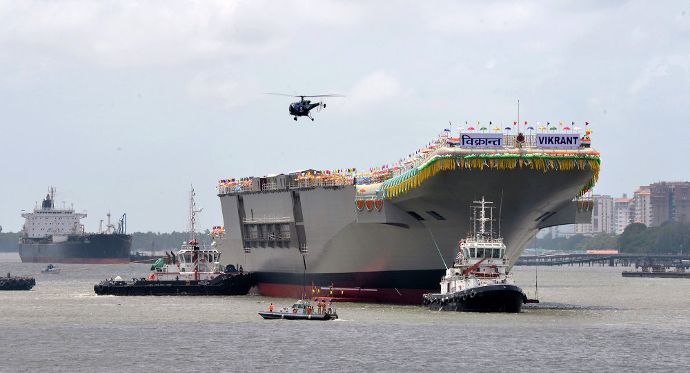 Tugboats guide the indigenously-built aircraft carrier INS Vikrant as it leaves the Cochin Shipyard Limited's dock after its launch in Kochi on August 12, 2013