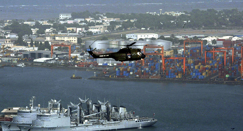 Helicopter flies over Djibouti harbour as part of city is seen, background