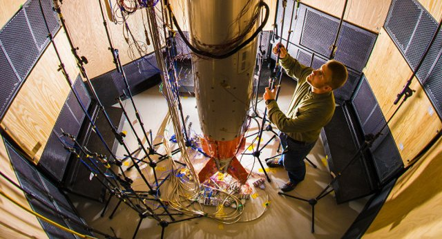 Sandia Labs mechanical engineer Ryan Schultz adjusts a microphone for an acoustic test on a B61-12 system