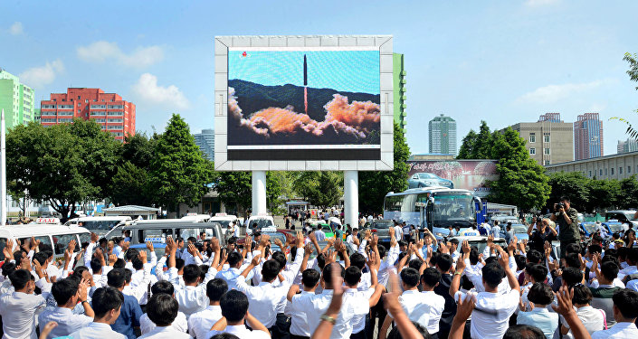 People watch a huge screen showing the test launch of intercontinental ballistic missile Hwasong-14 in this undated photo released by North Korea's Korean Central News Agency (KCNA), July 5, 2017