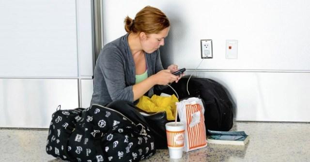 Mujer cargando el móvil en el suelo