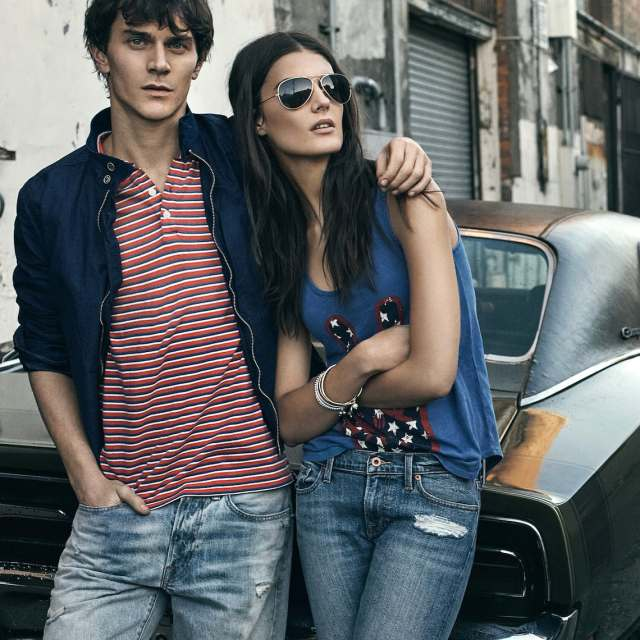 A couple wearing Lucky Brand apparel leans against the trunk of a vintage car in an alley