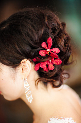 the brides romantic updo is plete with red flower hair pins photo by geoff white photography