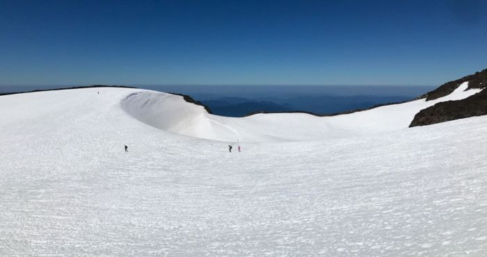 Hikers crossing a snow-filled South Sister cauldron