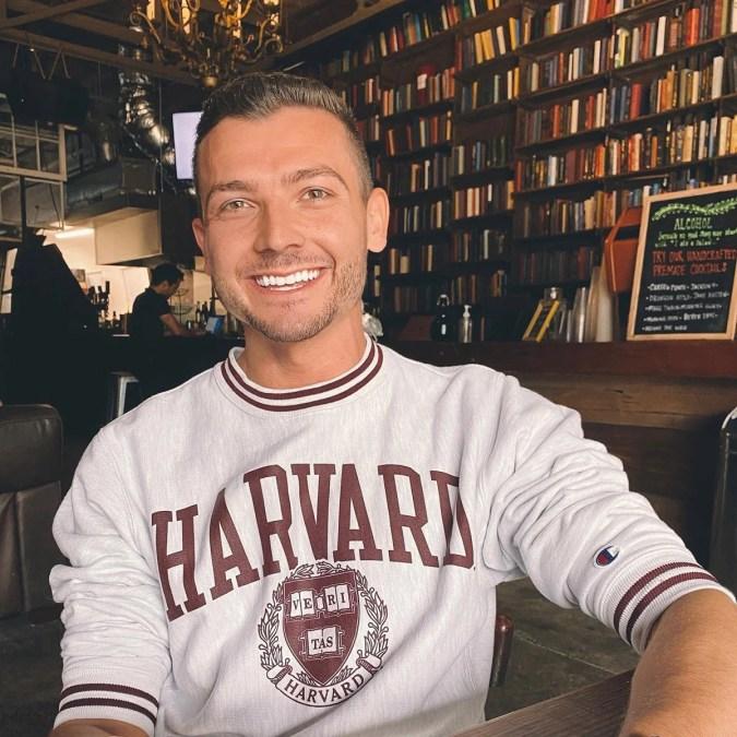 A student wearing a Harvard sweatshirt, smiling