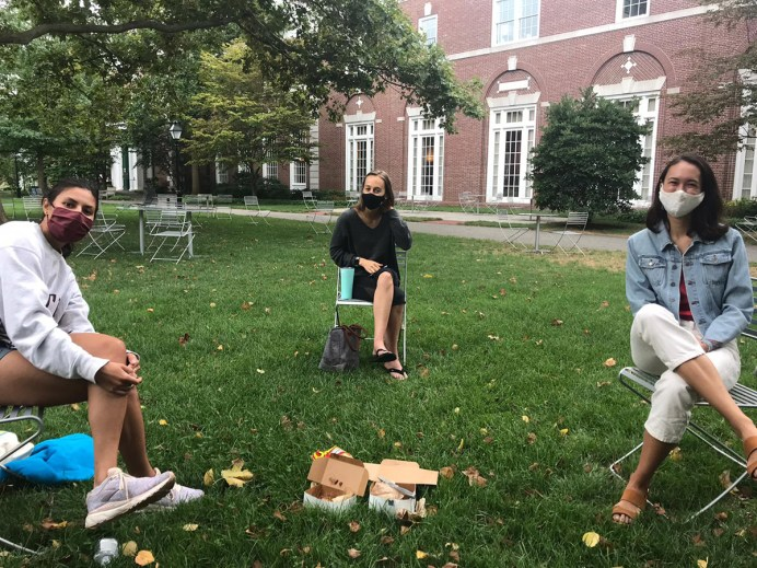 Three students sit with masks on socially distanced in Harvard Yard