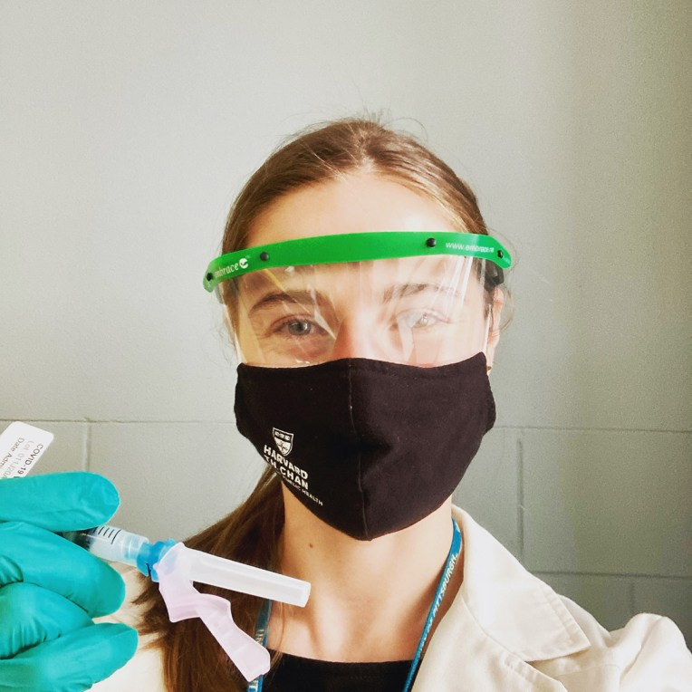 A student poses with a capped vaccine in PPE, wearing a Harvard Chan School mask