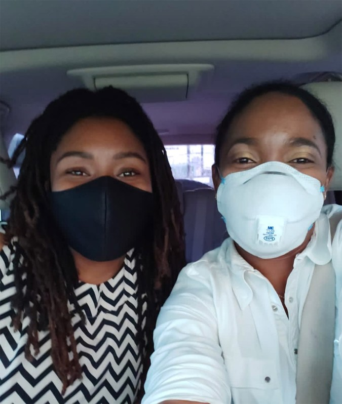 Two students pose together in car with masks on